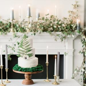An understated delicacy by Cake Expressions, Inc. features textural icing and a pairing of a single fern and anemone to top it off. Presenting it atop an earthy bed of moss adds an organic vibe to its minimalist simplicity.